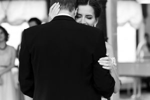 Happy newlywed bride and groom dancing at wedding reception closeup b&w