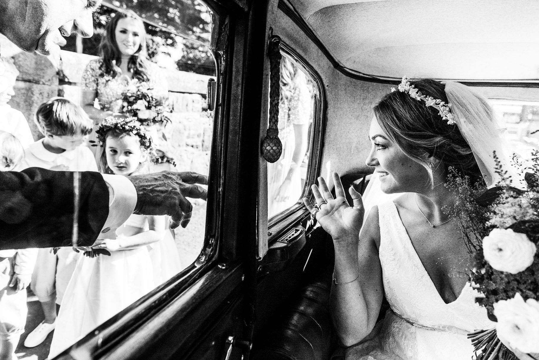 Black and white photo of bride arriving at church