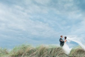 Bride and Groom on Scottish beach in Troon on a windy day