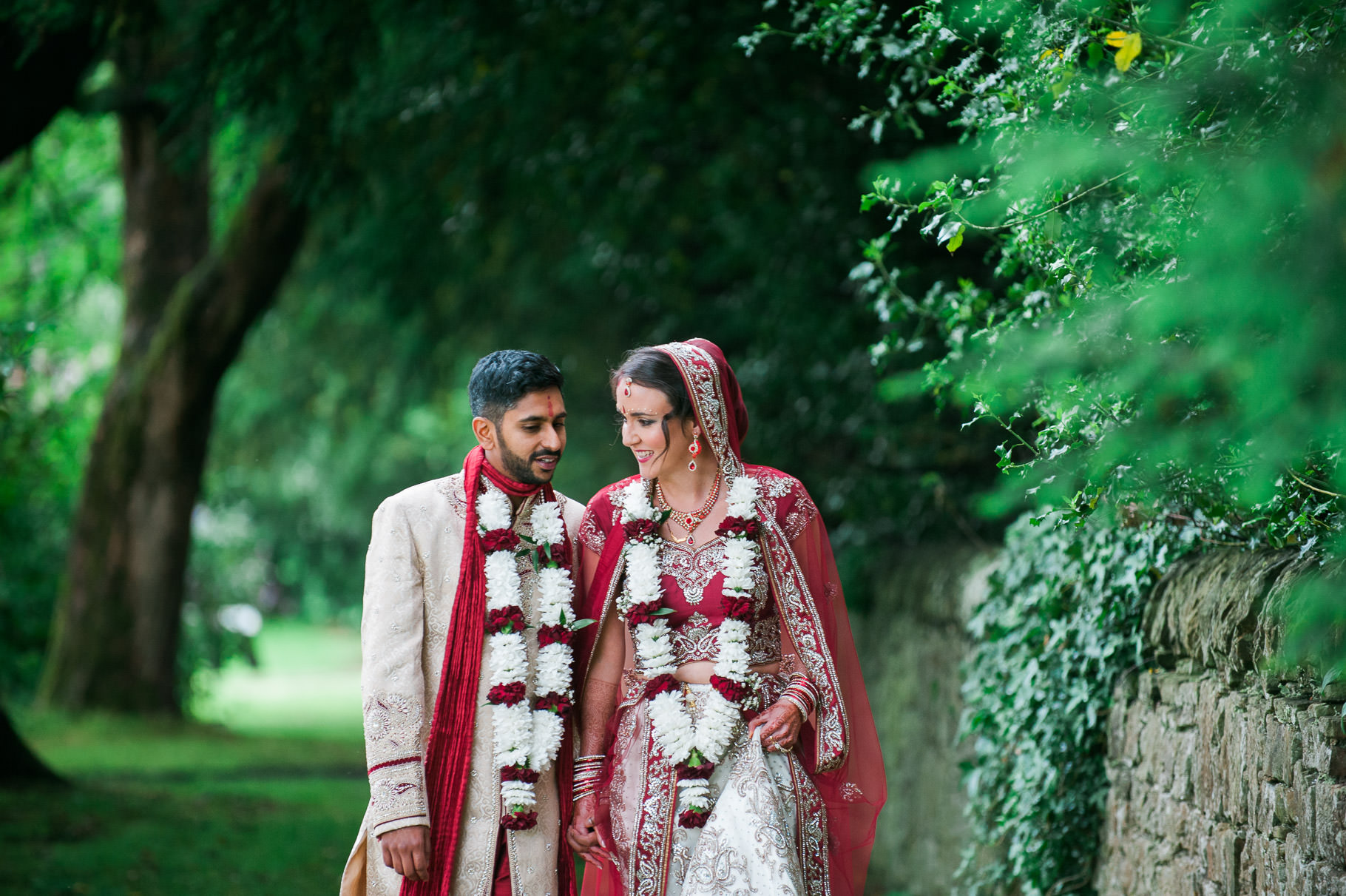 Indian Scottish bride and groom walking wearing traditional Indian wedding outfits