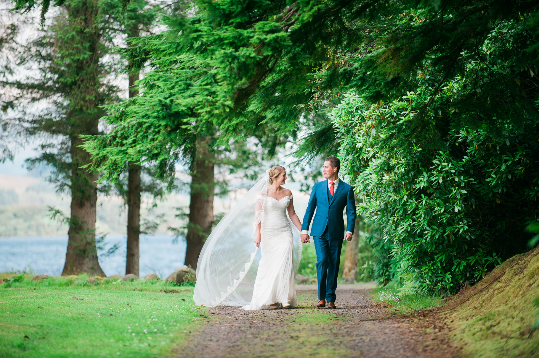 Scottish Highland Wedding by Loch Awe-bride and groom walking by loch awe-wedding veil