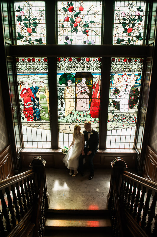 Bride and Groom sitting by stained glass window in One Devonshire Gardens, Hotel du Vin Glasgow