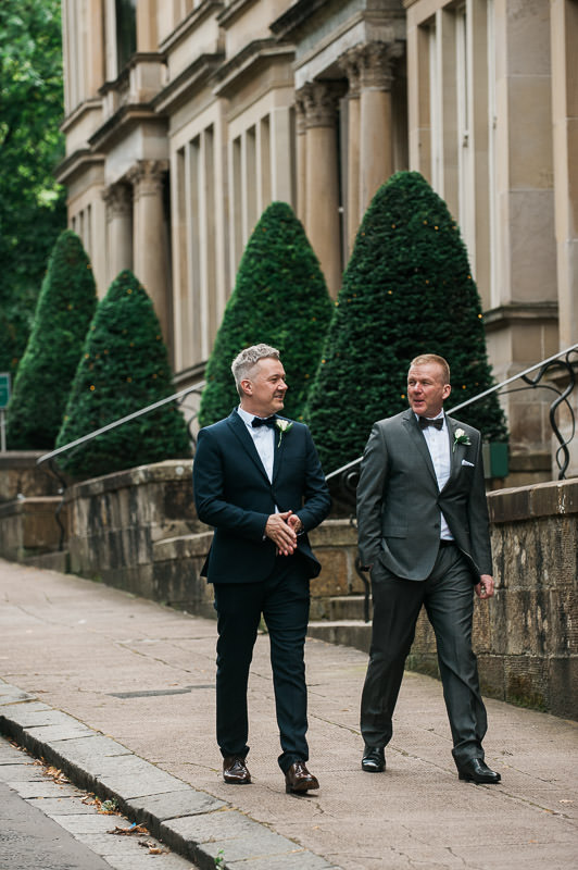 Groom and Best Man walking along the victorian terrace of One Devonshire Gardens in Glasgow