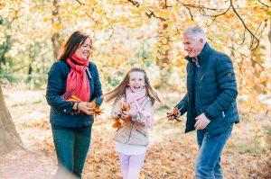 family fun in park with autumn leaves, autumn family portrait glasgow, parent and child fun portrait autumn glasgow