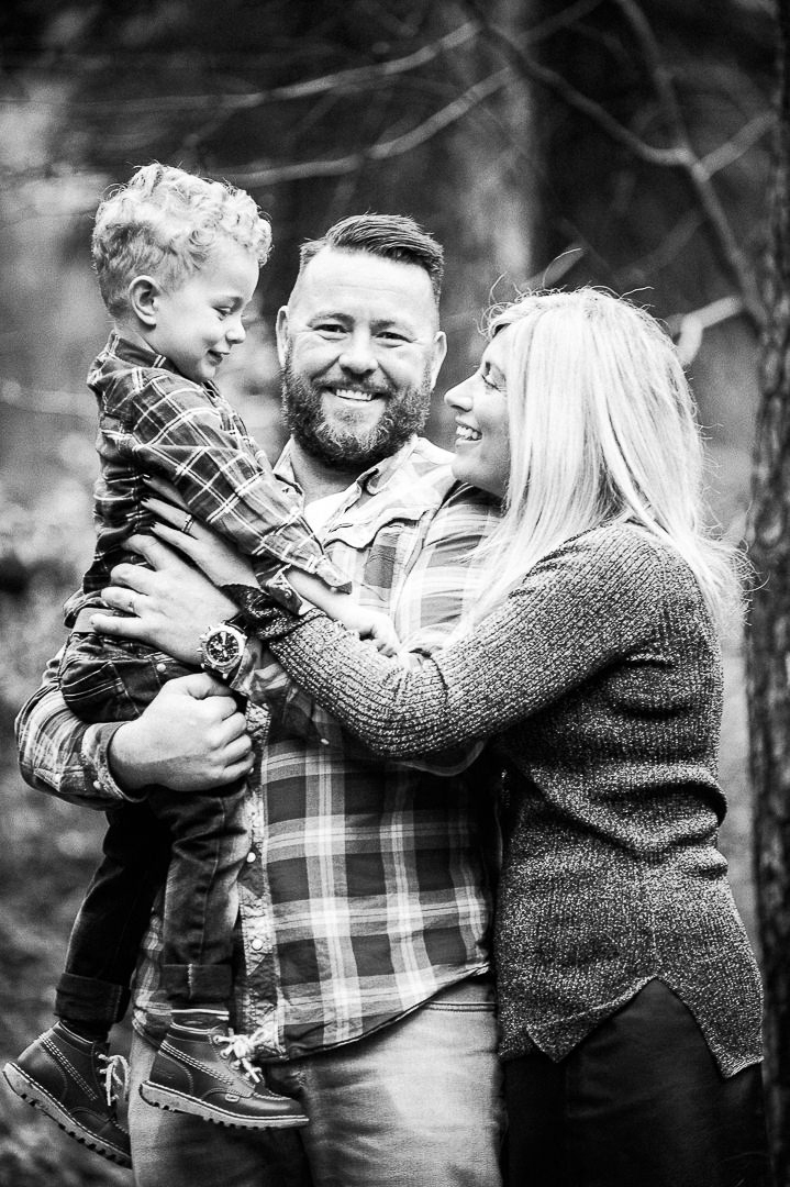 black and white photo of family, mum, dad and baby boy, laughing family portrait