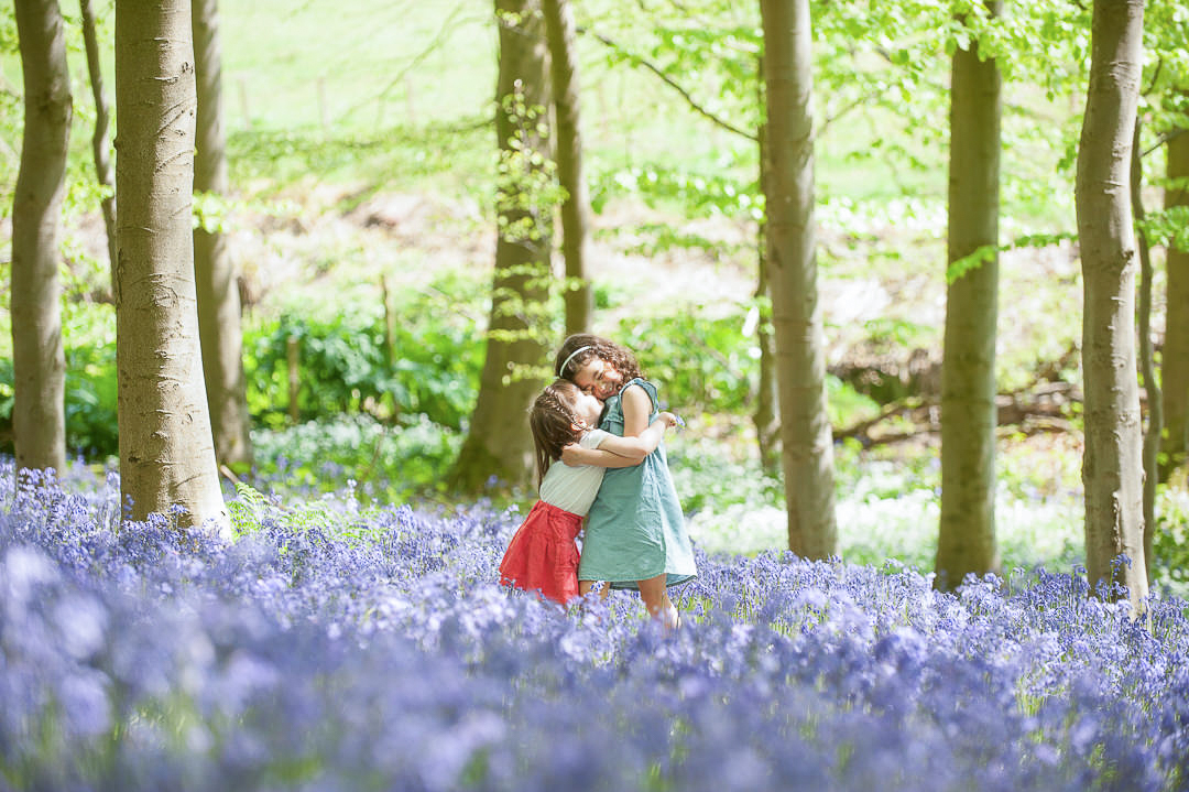 sisters hugging, sisiterly love, children in bluebells