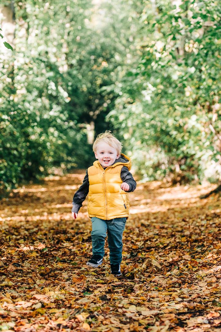 children playing in autumn leaves, glasgow pollok park in autumn, family portrait in glasgow, boy running in autumn leaves
