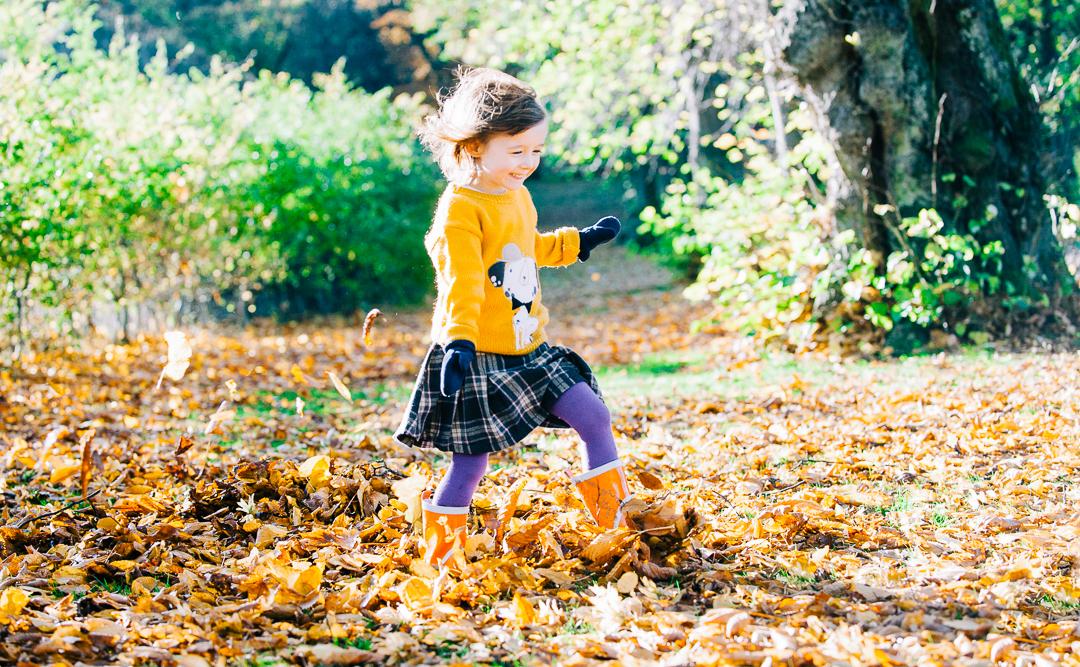 child kicking autumn leavesin glasgow, autumn childrens portrait