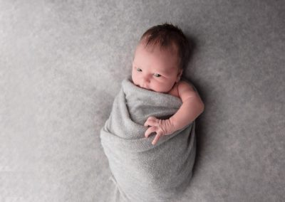 natural newborn photography, studio newborn baby photography, baby wrapped in grey swaddle